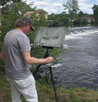 Chris Robinson painting by the river in the Dordogne